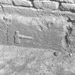 Il blocco con il simbolo dell'ascia a rilievo, ancora in opera nelle fondazioni della struttura.